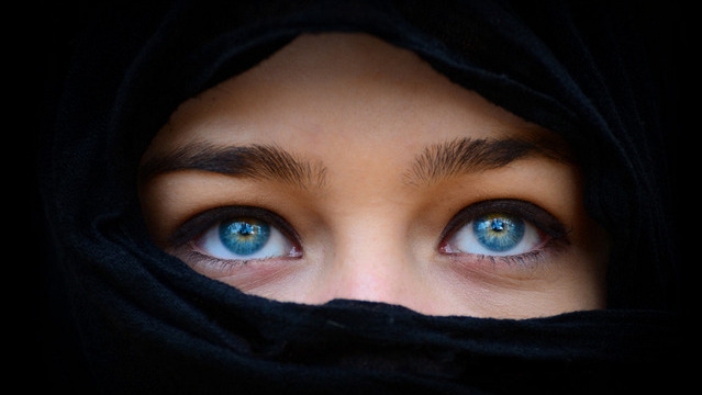 Beautiful blue woman eyes behind black scarf looking up